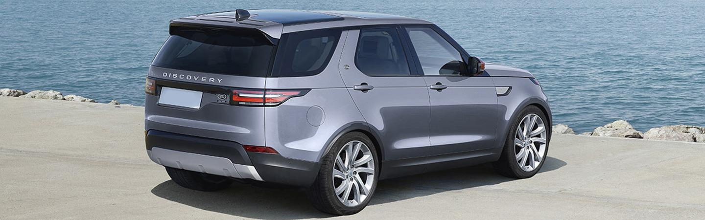 Rear view of the 2020 Range Rover Discovery parked outside next to the water