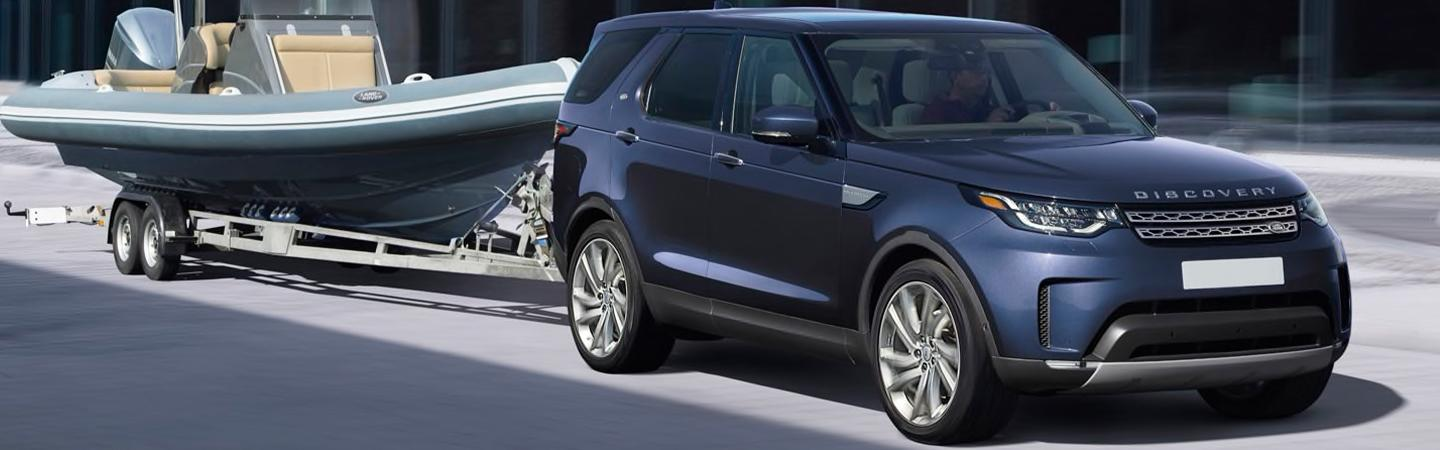 Side view of the 2020 Land Rover Range Rover towing a boat