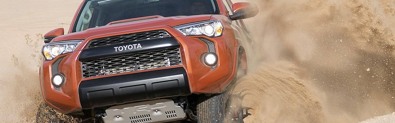Red 2020 Toyota 4Runner driving through dirt