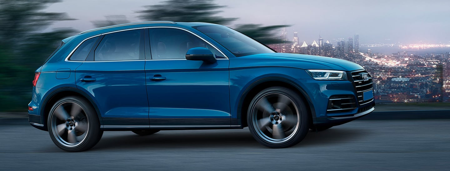 Passenger's side profile of blue Q5 in motion