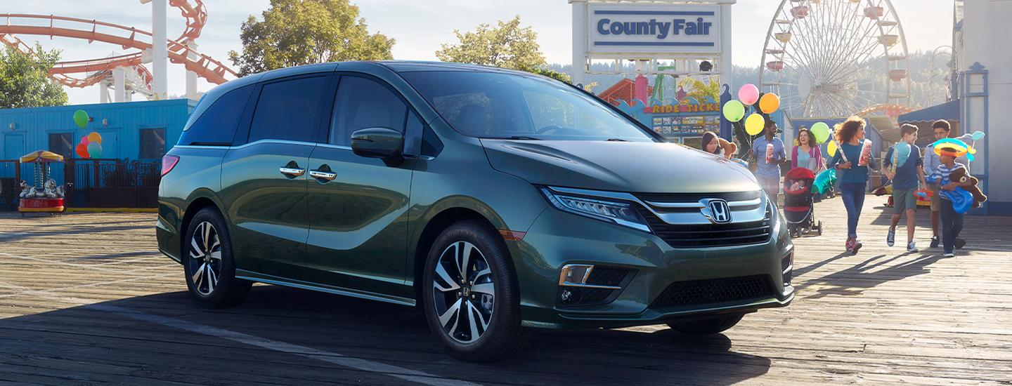 Front side view of the 2020 Honda Odyssey parked outside of a amusement park