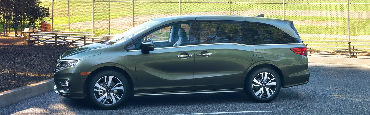 Side view of the 2020 Honda Odyssey parked next to a sports field