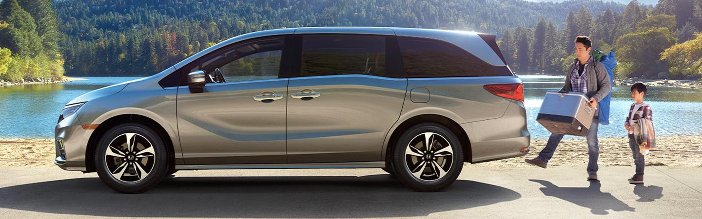 Side view of the 2020 Honda Odyssey parked next to a family
