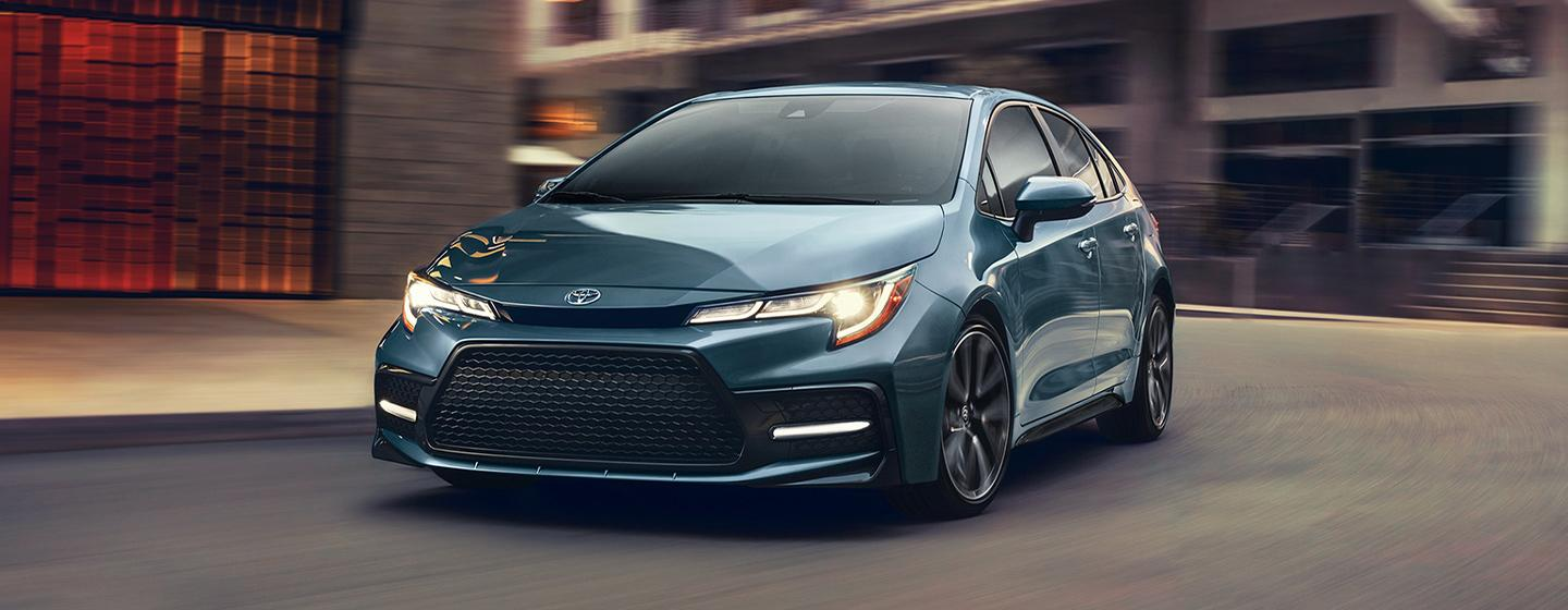 2020 Toyota Corolla turning on a road with the headlights on