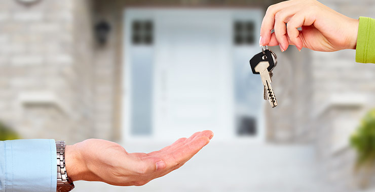 Two people handing keys