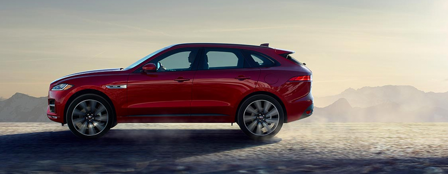 2019 Jaguar F-PACE driver side view driving on dirt.