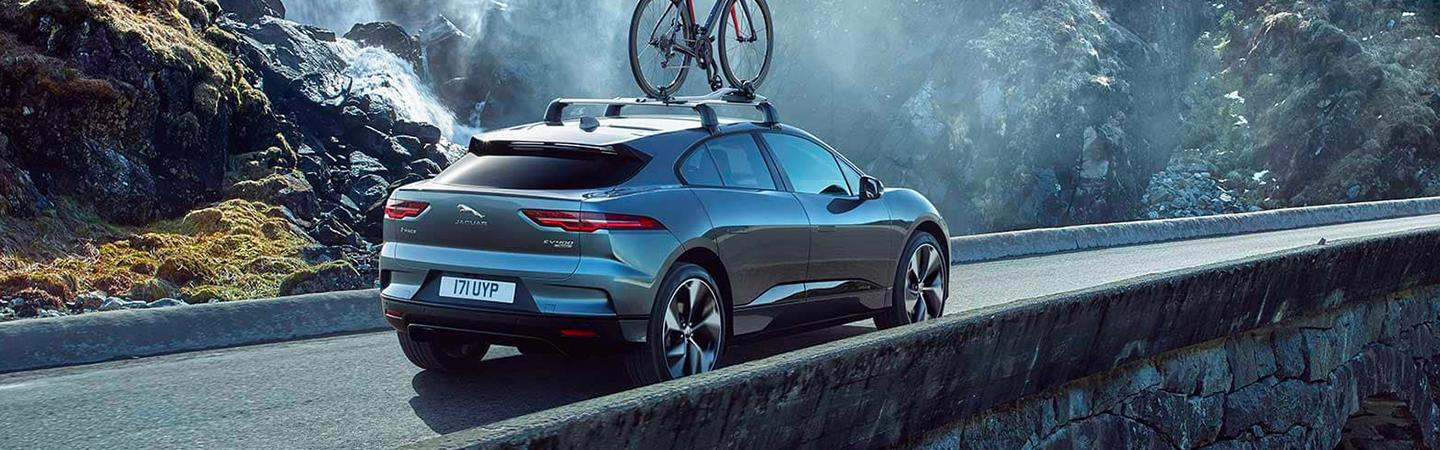 Rear side view of the 2020 Jaguar I-Pace in motion over a bridge