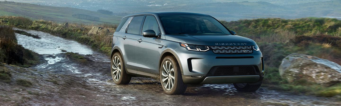Side view of the 2020 Land Rover Discovery driving through mud