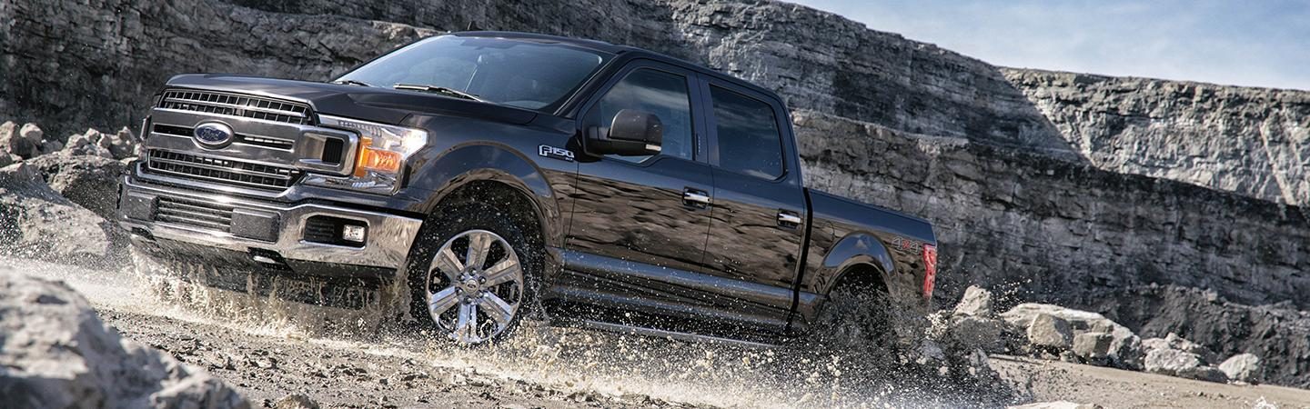 Side view of the 2020 Ford F-150 driving up the side of a rocky hill