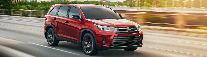 Red 2019 Toyota Highlander Hybrid in motion