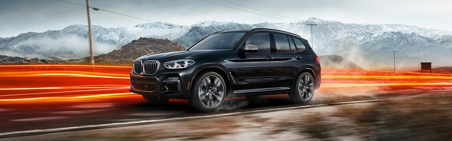 Side view of the 2020 BMW X3 driving forward