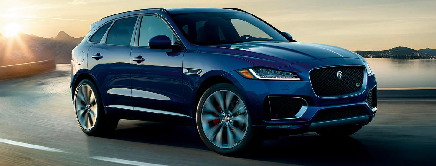 Side view of a blue 2020 Jaguar F-Pace in motion