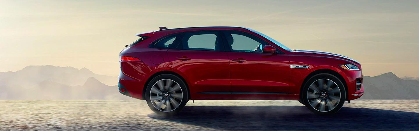 Side view of a red 2020 Jaguar F-Pace in motion