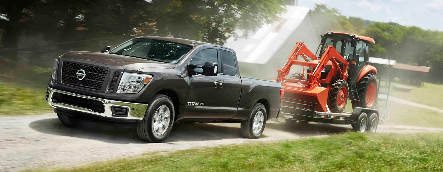 2019 Nissan Titan towing trailer with tractor.