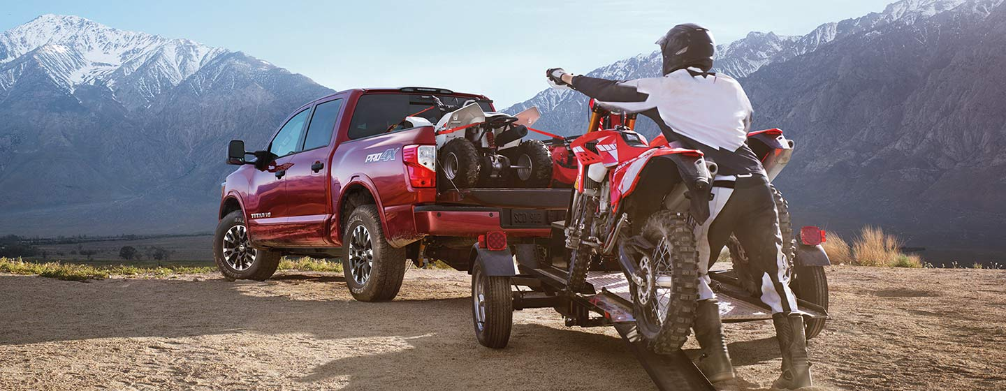 2019 Nissan Titan parked in mountains loading trailer with motorcycle.