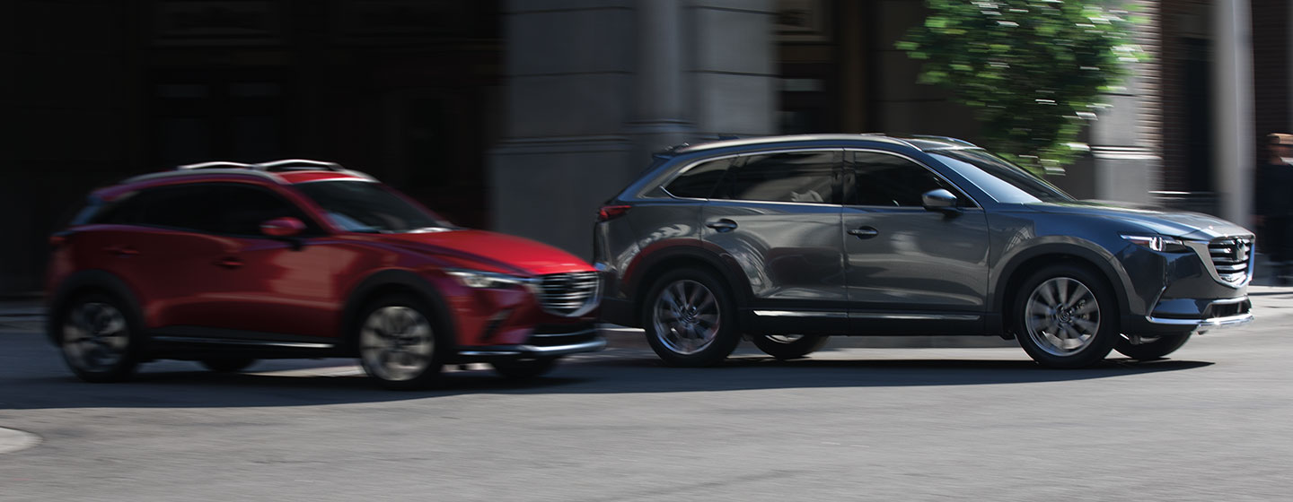 2019 Mazda CX-9 passenger side view driving in city in motion.