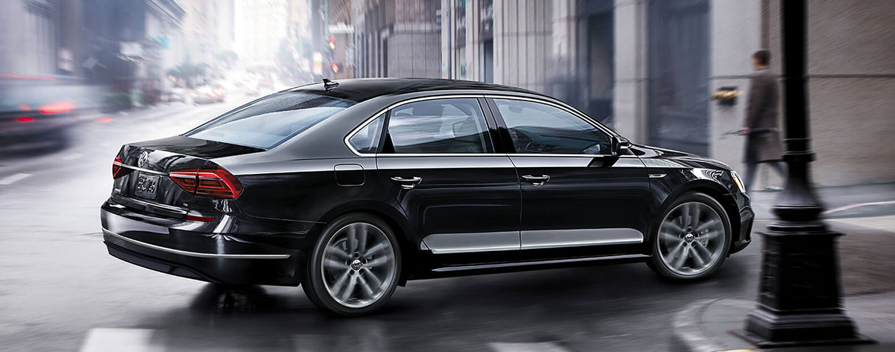 2019 Volkswagen Passat driving passenger side view taking corner in city.