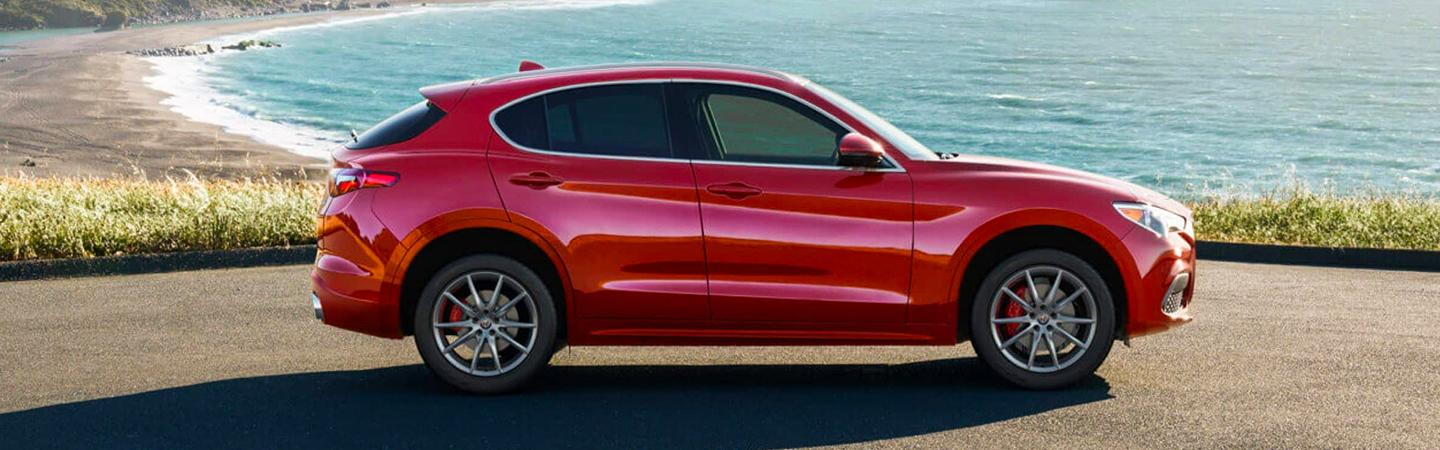 The red 2021 Alfa Romeo Stelvio parked on a cliff overlooking the ocean