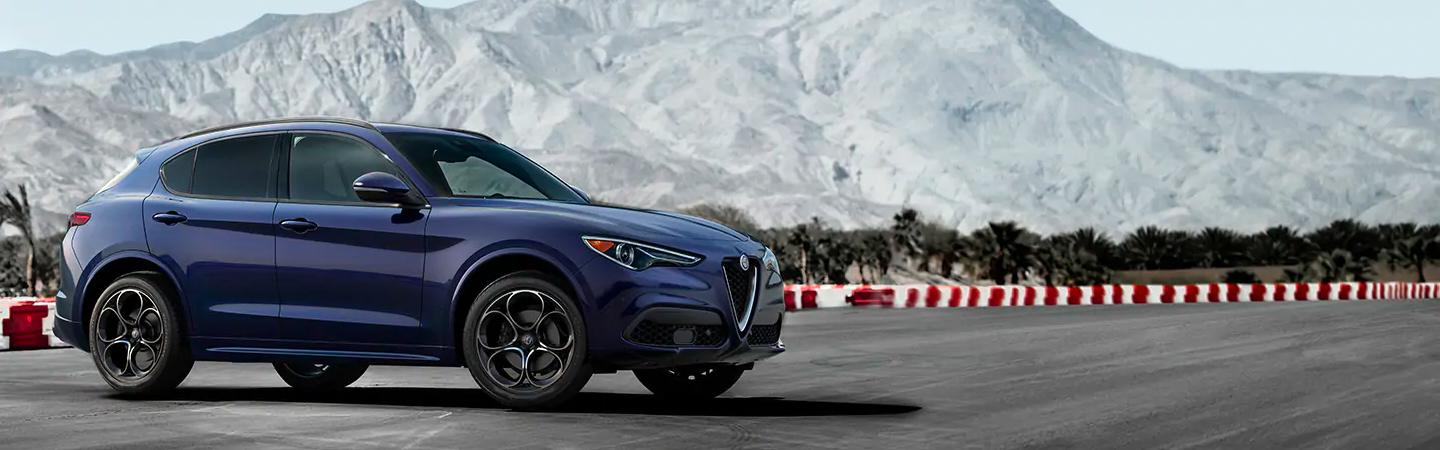 Navy blue 2021 Stelvio parked next to race track safety barriers