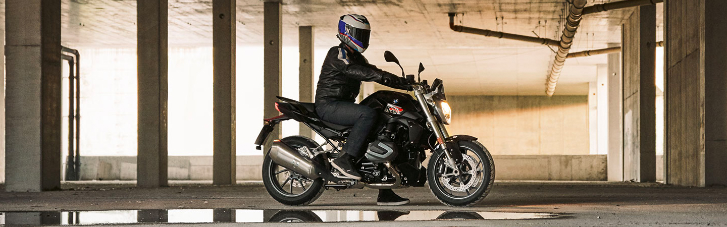Side view of the 2020 BMW 1250 R parked inside with a rider