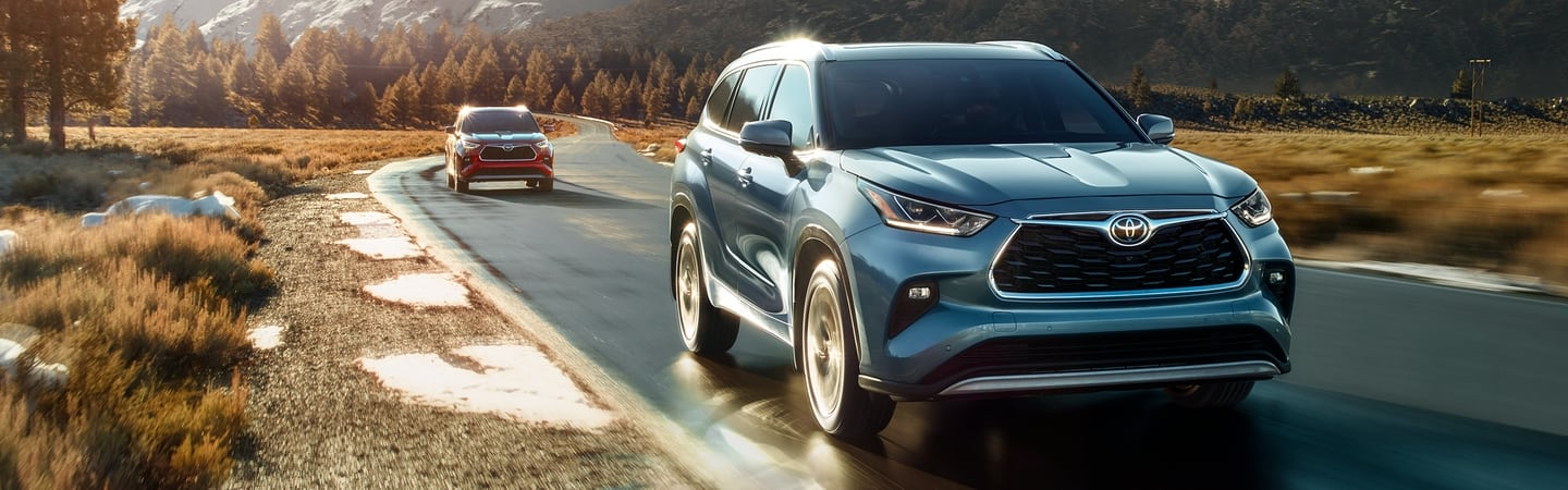 Two 2020 Toyota Highlander vehicles driving on a road