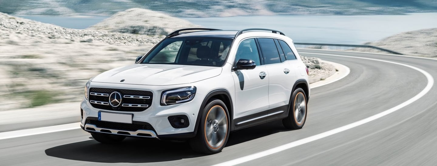 White Mercedes-Benz GLB driving by the ocean.