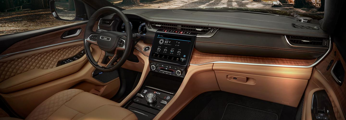 Passenger-side view of the Jeep Grand Cherokee steering wheel, infotainment system, and dash