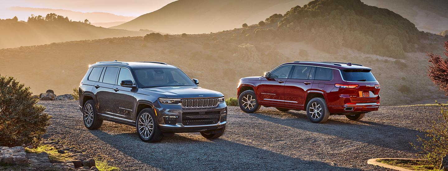 Front view of a grey 2021 Jeep Grand Cherokee and back view of a red 2021 Jeep Grand Cherokee parked on a cliff in the mountains.