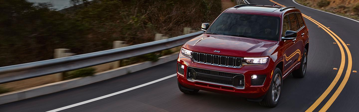 Front view of a red 2021 Jeep Grand Cherokee driving down the road