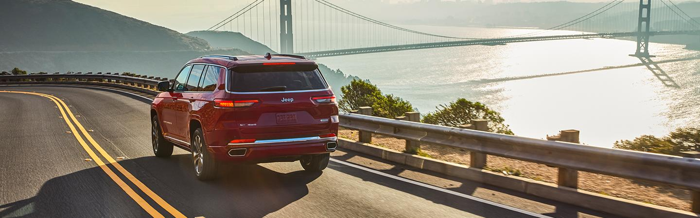 Rear view of a red 2021 Jeep Grand Cherokee driving near the Golden Gate Bridge