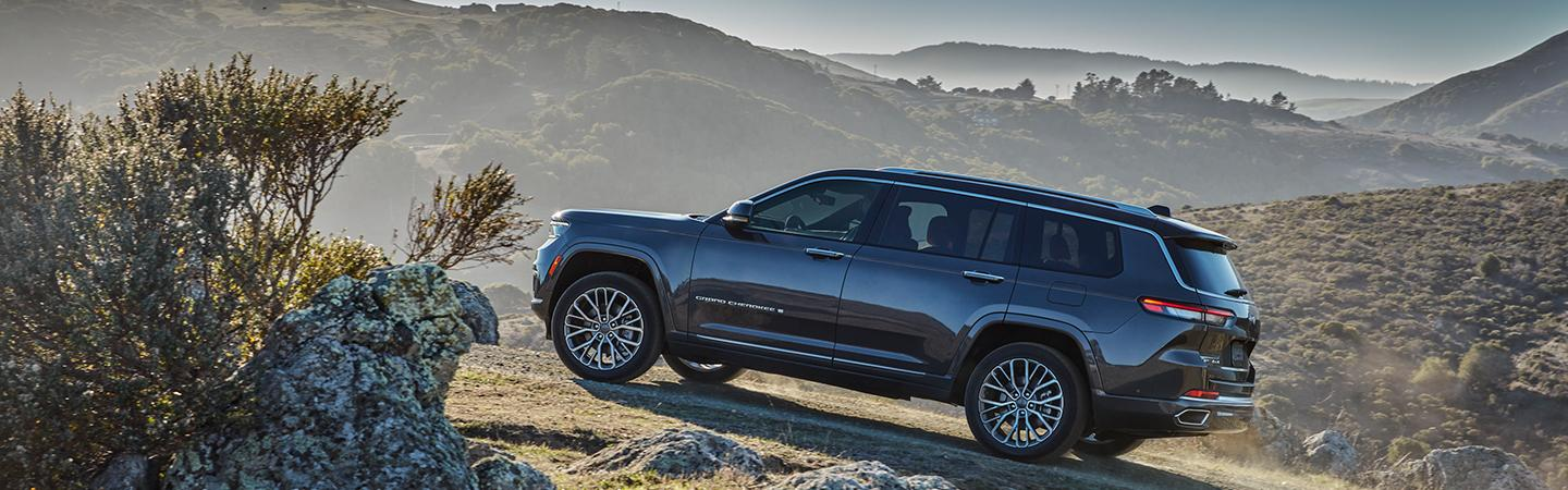 Side view of a blue 2021 Jeep Grand Cherokee in the mountains