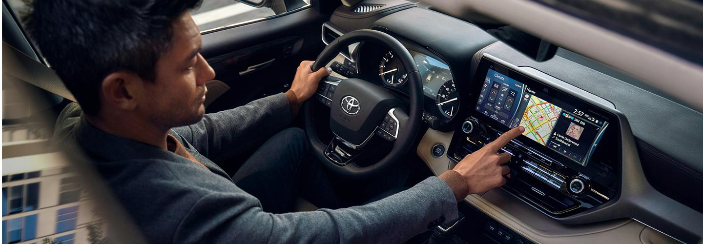 Driver using the touchscreen display in the 2020 Toyota Highlander