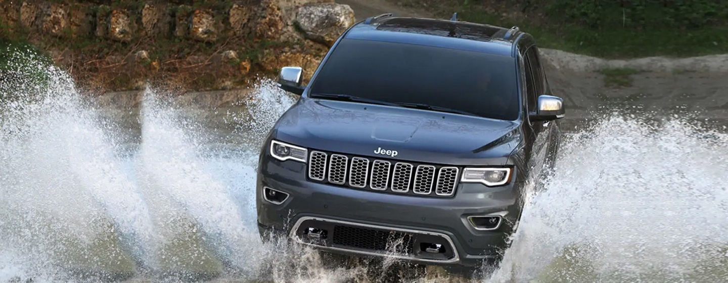 2019 Jeep Grand Cherokee front view driving through water levy.