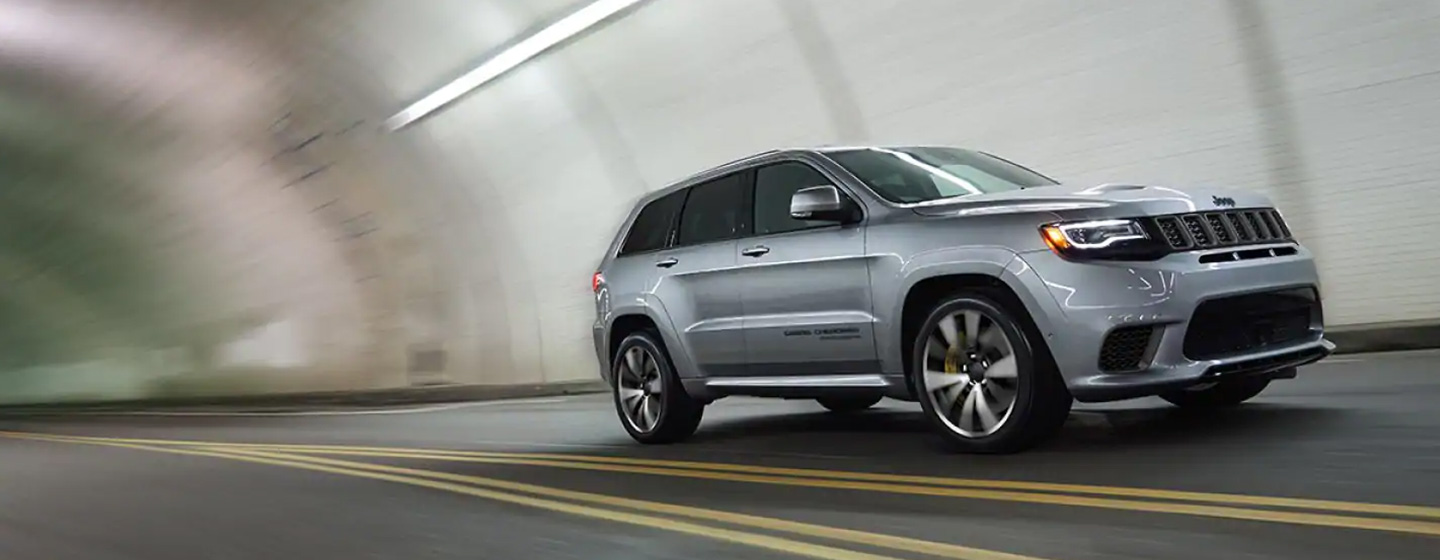 2019 Jeep Grand Cherokee driving in a tunnel front passenger side view.