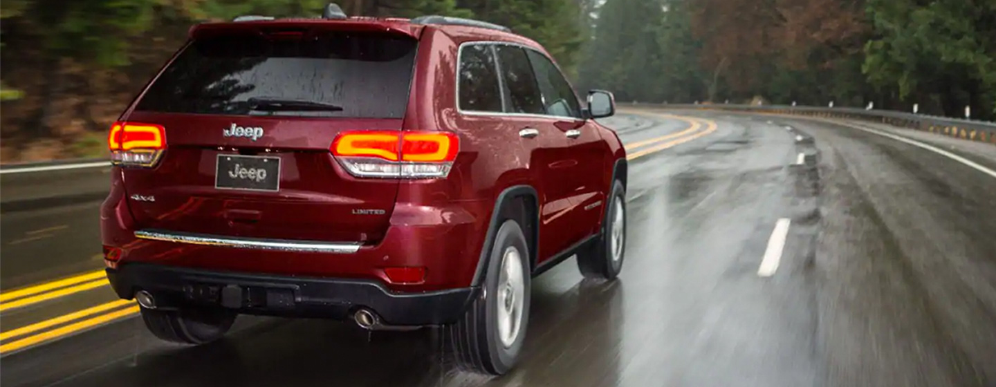2019 Jeep Grand Cherokee rear view driving in rain mountian highway.
