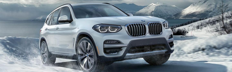 White 2021 BMW X3 Driving Through Snow
