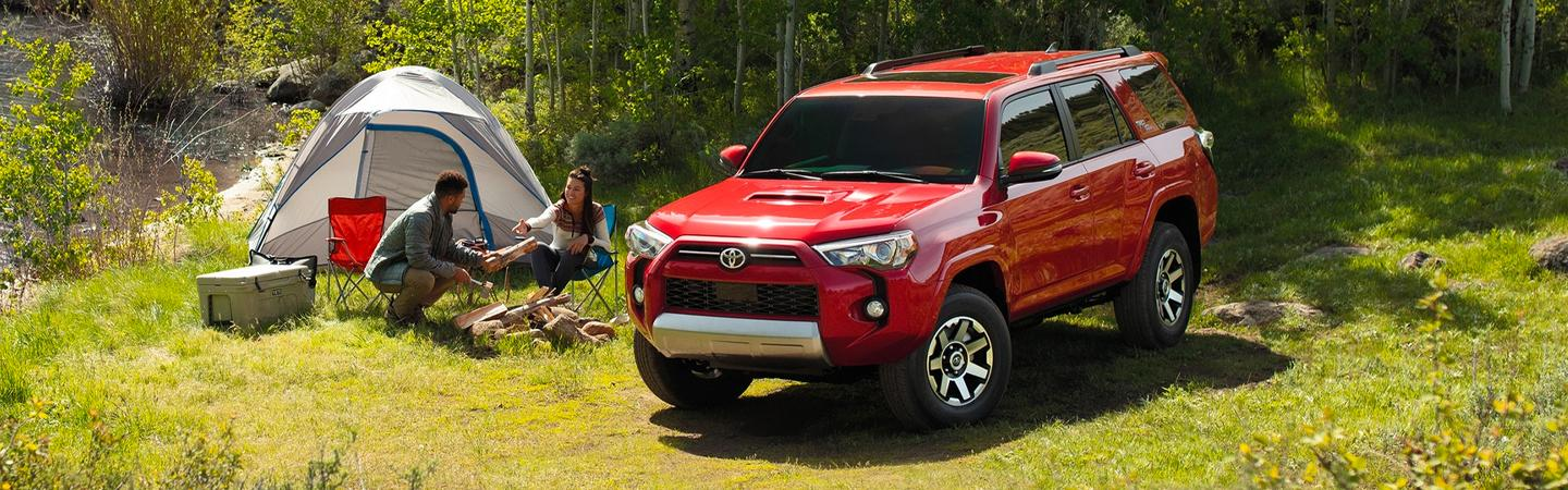 Red 2020 Toyota 4Runner parked in a field of grass