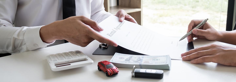 A salesman and customer signing paperwork at desk