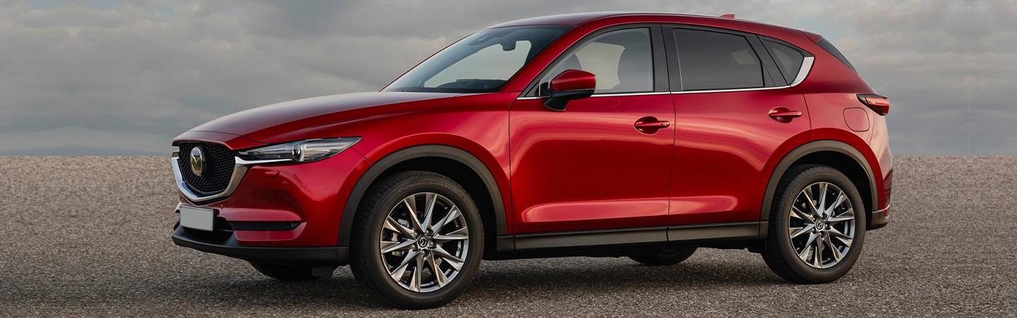 Driver side view of a red 2021 Mazda CX-5 parked