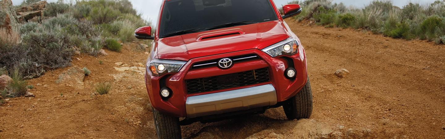 Red 2020 Toyota 4Runner driving on a dirt road