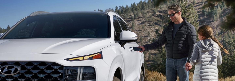 A driver and child near their white Hyundai vehicle