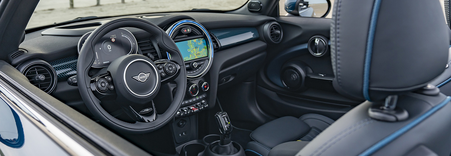Driver's side window view of a MINI Cooper Convertible's steering wheel and dashboard