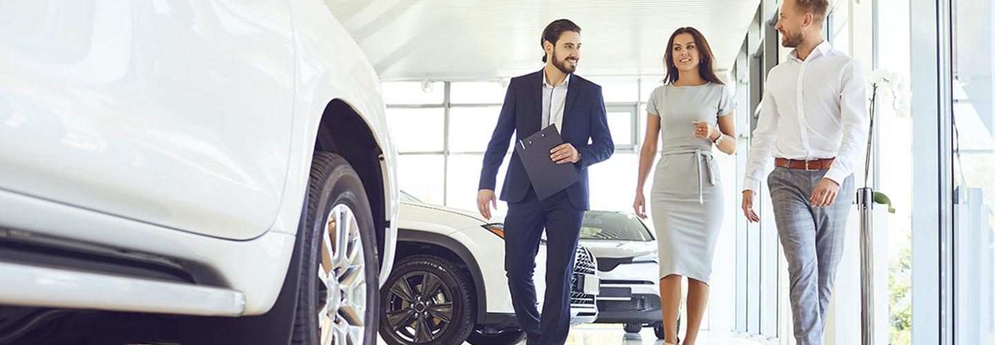 Salesman showing a couple a new vehicle.