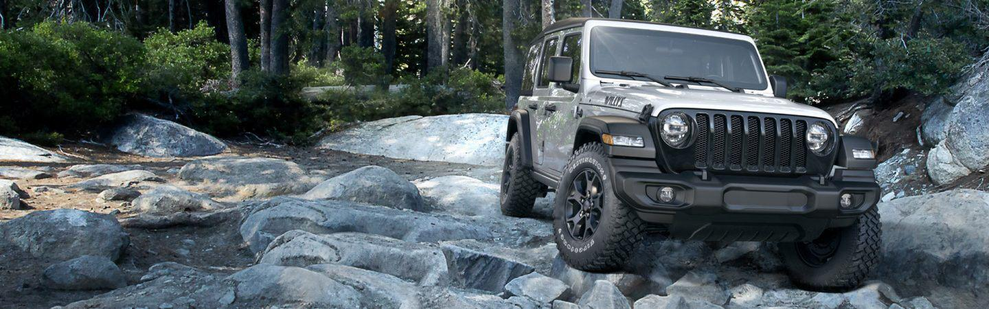 Front view of the 2020 Jeep Wrangler off roading over a stream
