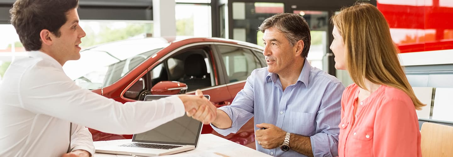 Couple purchasing a vehicle from a finance representative