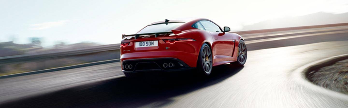 Rear view of the 2020 Jaguar F-Type driving through a turn