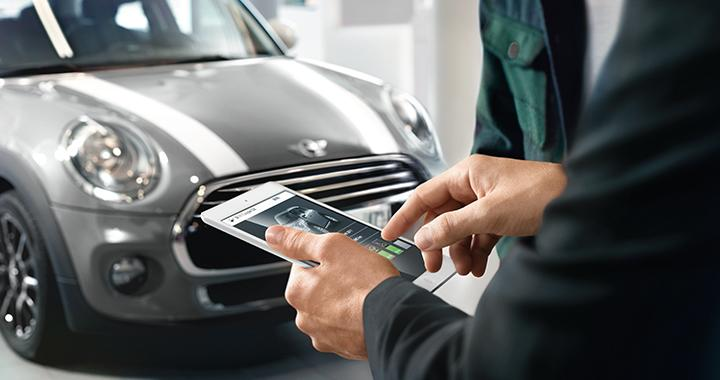 Driver looking at a MINI phone application outside of their car