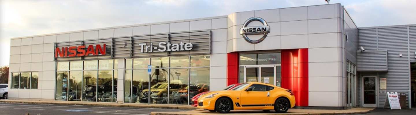 Orange Nissan 370z in front of the Tri-State Nissan dealership