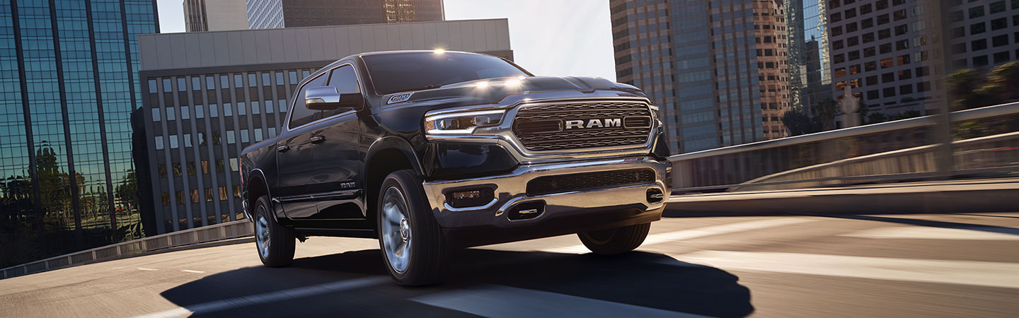 Front view of a black 2021 RAM 1500 driving through the city