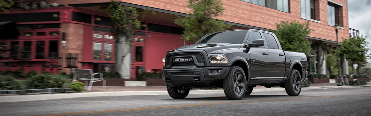 Side view of a black 2021 RAM 1500 driving down the road